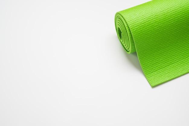 Зеленый коврик для йоги на белом