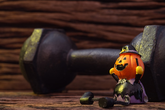 Праздник хэллоуина, голова кукла тыквы преследуют жуткий и черный железный гантель
