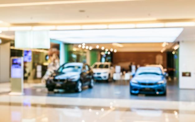 Аннотация размытым автомобиль. изображение нерезкости автомобиля в пользе выставочного зала для предпосылки.