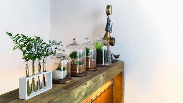 テラリウムの瓶、古い木製の棚、ビンテージガラス瓶の中の花の小さな庭