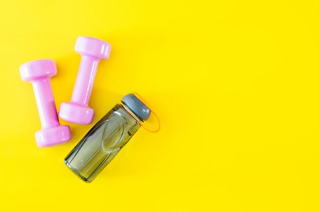 ピンクのダンベルと黄色の背景に水のボトルの平面図です。フィットネスや健康的なライフスタイルの背景のコンセプトです。