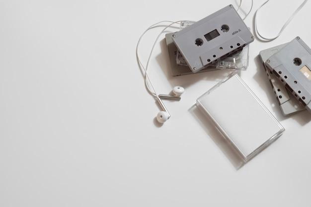 白い背景の上のイヤホンとレトロな古いオーディオカセットテープのオーバーヘッドショット、フラットコピースペース平面図を置きます。