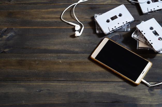 スマートフォンと木製の背景にカセットテープ。現代とレトロの技術背景コンセプトです。コピースペース平面図。