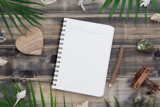 ハート形の岩、貝殻、ヤシの葉、飛行機モデルとフラットレイアウト空白のメモ帳。