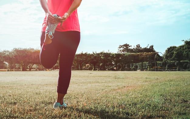 足のストレッチ体操をしている女性。
