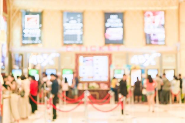 Размытым фоном люди покупают билеты в автомате по продаже фильмов