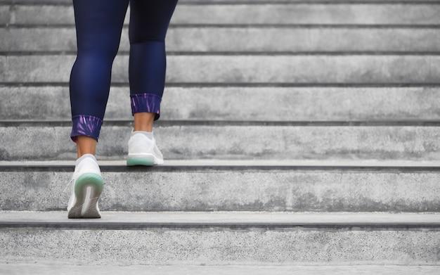 階段を上ることをやっている女性ランナーの運動選手。