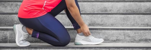 練習前にランニングシューズに靴ひもを結ぶ女。トレーニングの準備をしているランナー。