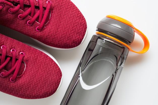 赤いスポーツシューズと水のボトル。アクティブな健康的なライフスタイルの背景。