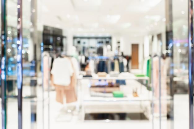 背景として布ストアの抽象的なぼやけた入り口エリア。衣料品店の正面がぼやけています。