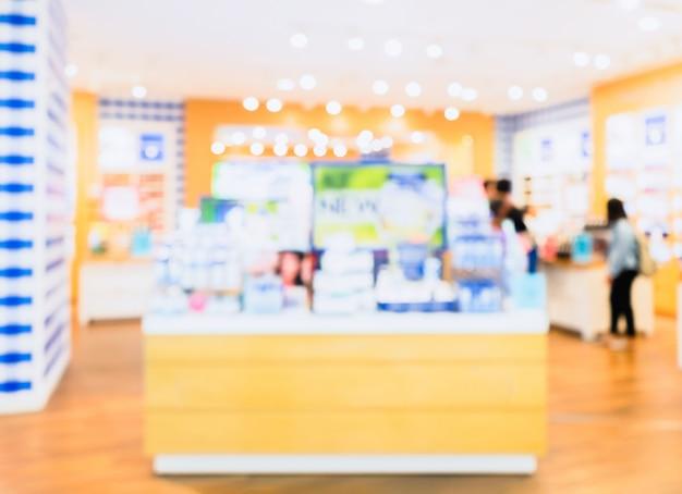 背景のボケ味を持つ化粧品店のカウンターの抽象的なぼやけた写真