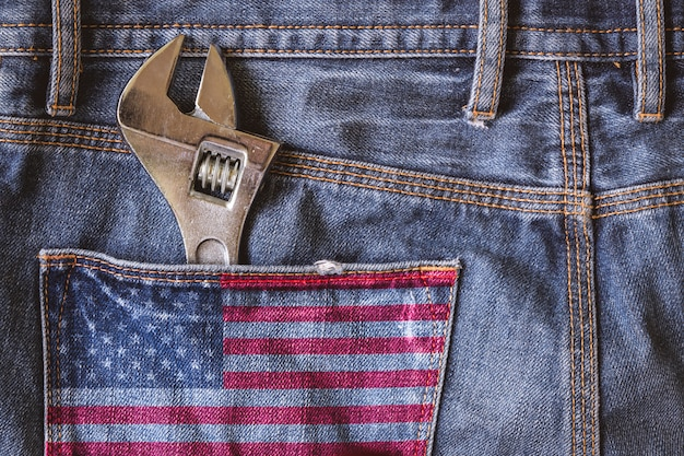 アメリカ国旗のあるブルージーンズの後ろポケットにある調節可能なレンチ
