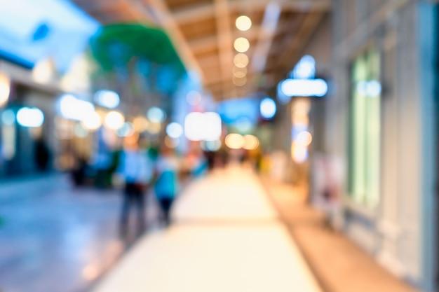 Затуманенное ходьбе людей в центральной торговой улице в сумерках с боке