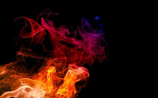 カラフルな火と煙で暗い黒の背景に分離された光テクスチャ抽象