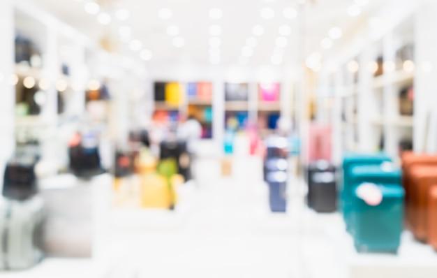 抽象的なぼかしスーツケースと美しい高級ショッピングモールインテリアの旅行バッグストア