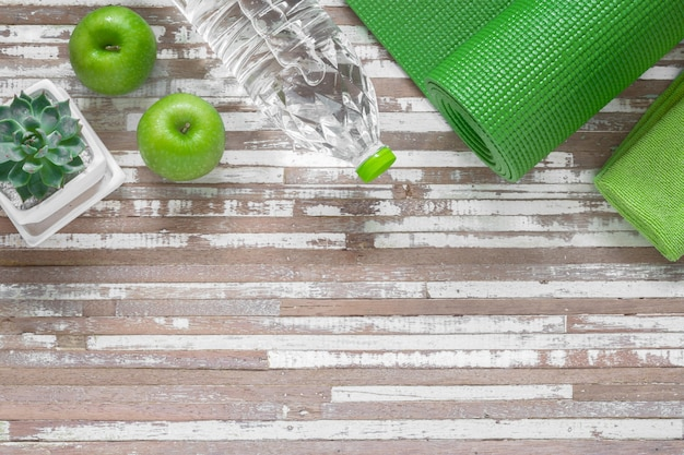 緑のマット、緑のタオル、水のボトル、青リンゴでヨガの練習をします。
