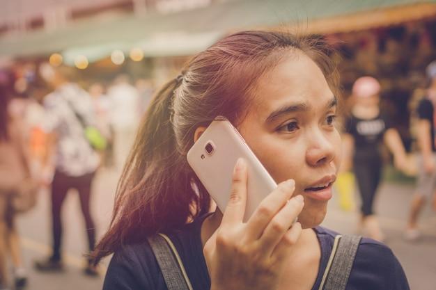 若い女性アジアの旅行者は市場で電話を使う