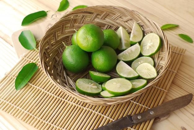 竹マットの上のナイフが付いているバスケットのグリーンレモンスライスとグリーンレモン。
