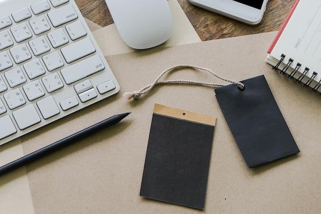 無料のラベルとコンピューターのキーボードと古い木材の背景に鉛筆と紙のシートとノートブック