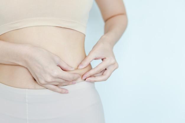 女性は、腹部の脂肪をどのように減らしたかを見るために、胃の脂肪を捕まえます。腰の脂肪層をテストする女の子