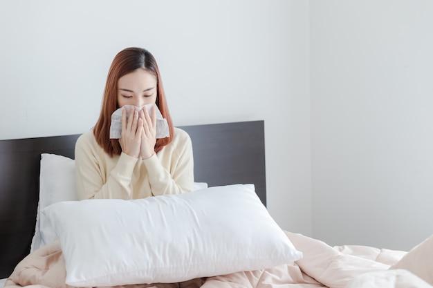 若い女性は黄色のセーターを着る鼻アレルギー、自宅のベッドに座っている鼻くしゃみをしたインフルエンザ