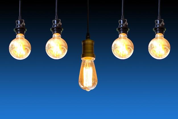 濃い青の背景、アイデアコンセプトに掛かっているヴィンテージ電球。