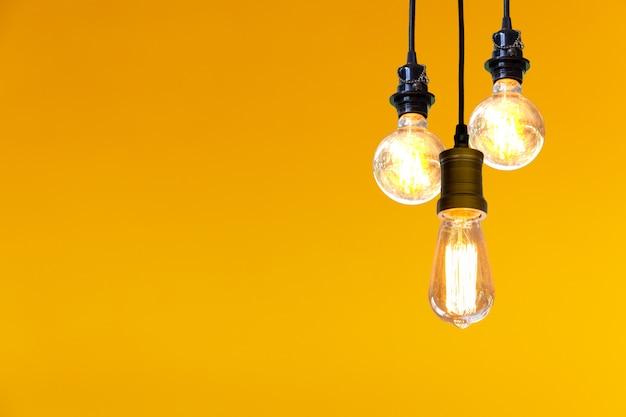 黄色の背景の上にぶら下がっているビンテージ電球