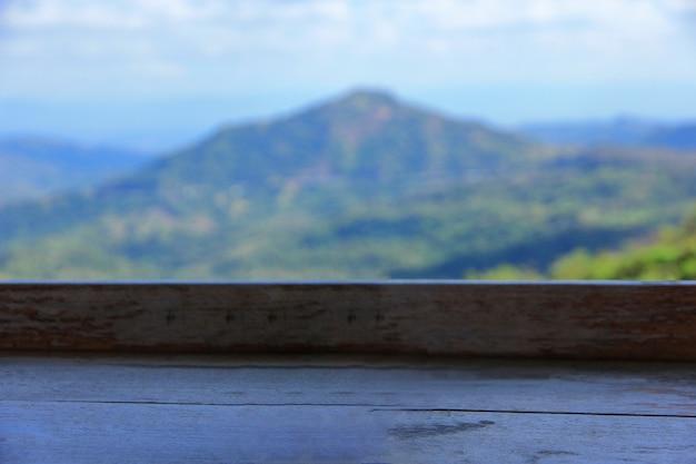 緑の山の風景をぼかした写真を木製のテーブル