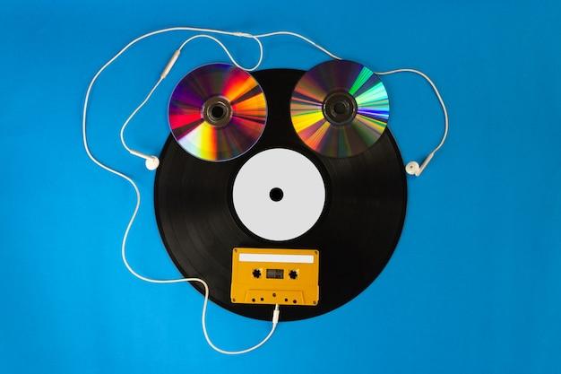 Старые виниловые пластинки и компакт-диск с аудиокассетой создают форму робота и наушников на синем фоне