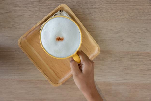 木のテーブルに泡とカプチーノコーヒーのカップを持っている手