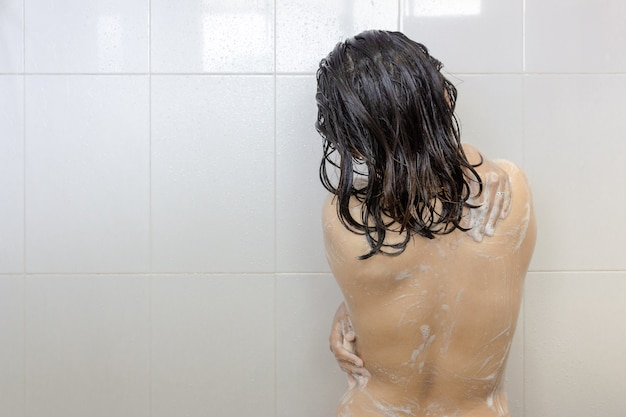 シャワーを浴びて、白いバスルームに石鹸をこすりながら若いアジア女性