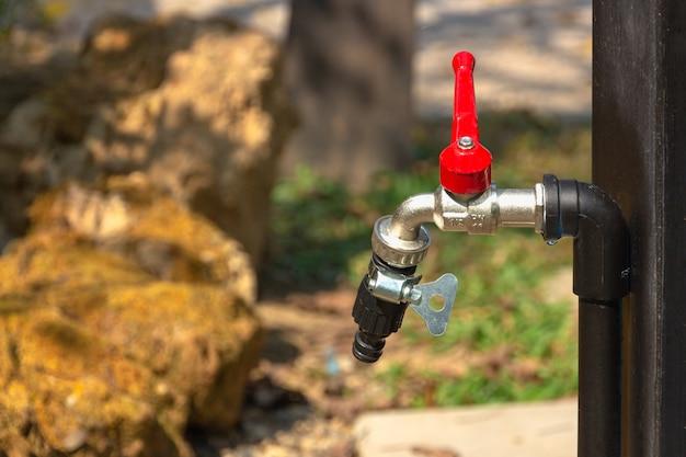 Красный водопроводный кран на фоне природы