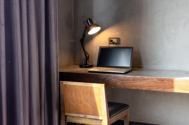 部屋のテーブルの上にランプが付いているラップトップ