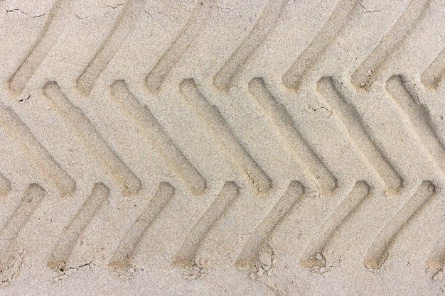 タイヤは、砂浜のトラクターの足跡、背景のための砂のテクスチャ。