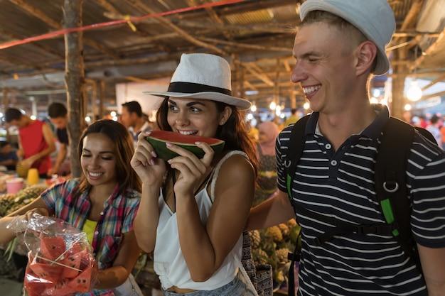 アジアの伝統的なストリートマーケットでスイカを味わう友人の観光客