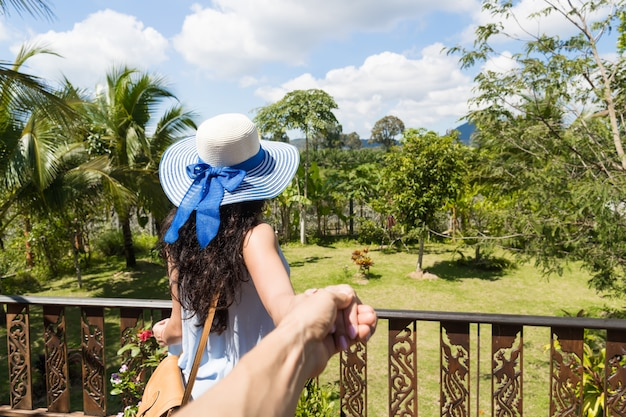 美しい熱帯の風景の上の帽子の若い女性の背面図