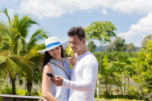 熱帯の森林ビュー上のセルのスマートフォンと若いカップル