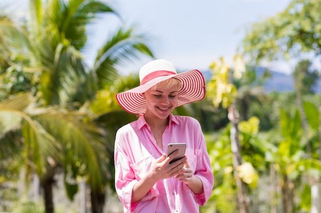 熱帯の森の上の携帯スマートフォンを持つ若い女性メッセージング