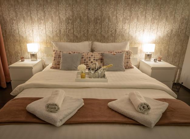 ランプとベッドサイドテーブルを含む寝室の設定とビンテージのホームインテリア。グレーの配色。サテン仕上げの寝具