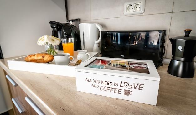 Кухонный стол. бытовая техника. утро, кофе, эспрессо, апельсиновый сок, круассан, цветок