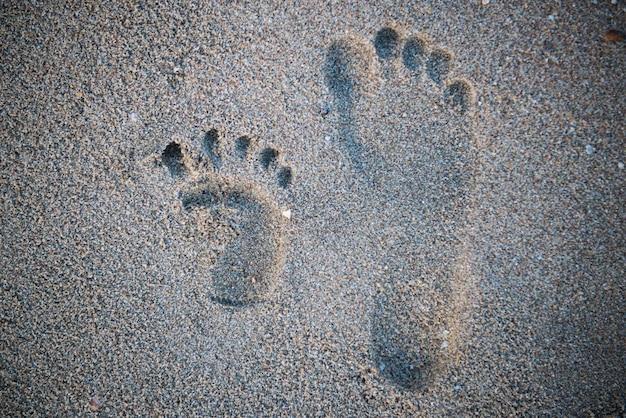 Закройте фотографию правой человеческой следы рядом с детским следом на тропическом песчаном пляже.