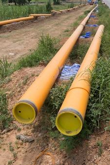 黄色のプラスチック製のパイプ移送用水システムが現場に整列している。