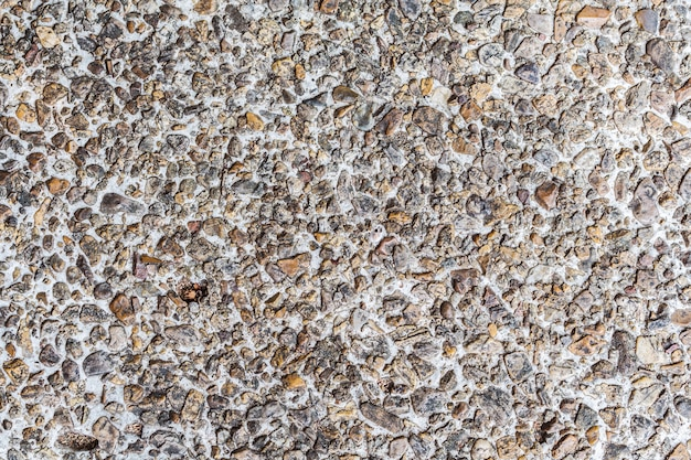 小さな砂の石の壁のテクスチャの壁