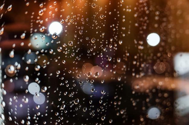 Капли дождя на окне ночью.
