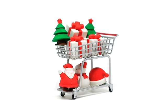 Магазинная тележкаа с элементом украшения для рождественской вечеринки изолированной на белой предпосылке.
