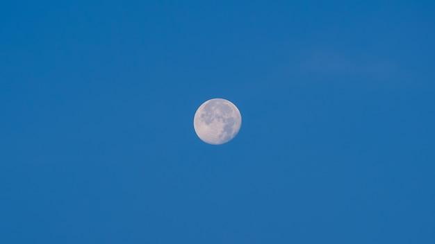 昼間の青い空に満月。