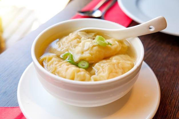 中華レストランの木製のテーブルの上の白いセラミックボウルでエビ団子スープ。