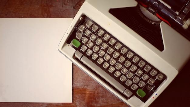 Вид сверху пишущей машинки и пустой бумаги на офисном столе