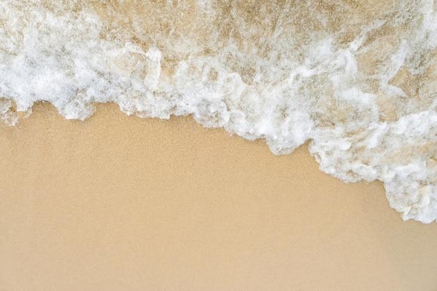 海は海岸線にキスし続け、コピースペースのある砂の上に白い波が見えます。