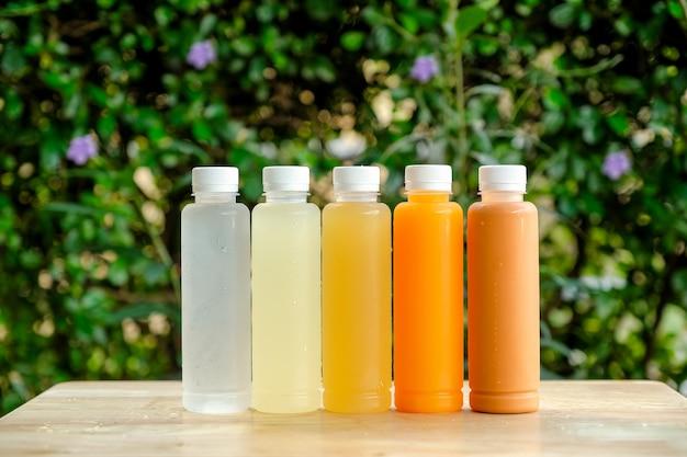 木製のテーブルの上の明確なプラスチック製のボトルのマルチフレーバージュース。
